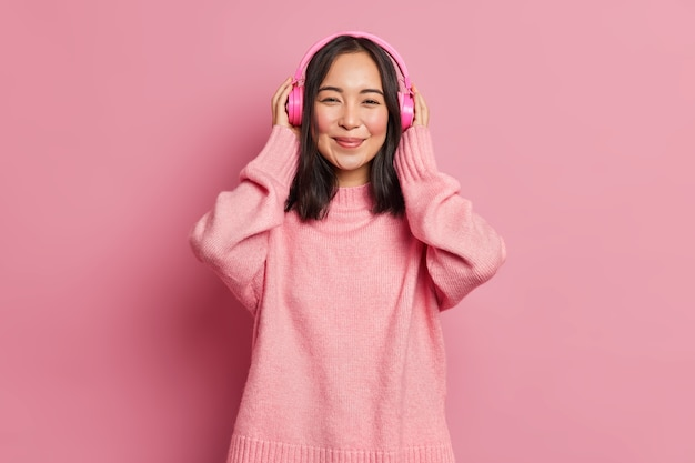 Porträt der schönen asiatischen weiblichen meloman trägt drahtlose elektronische stereo-headpones lauscht lieblings-audio-track oder beliebte song-recreats mit guter musik genießt ruhige melodie trägt rosa pullover