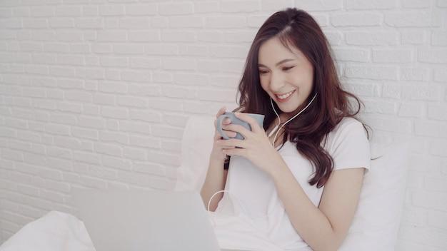 Porträt der schönen attraktiven asiatin, die computer verwendet