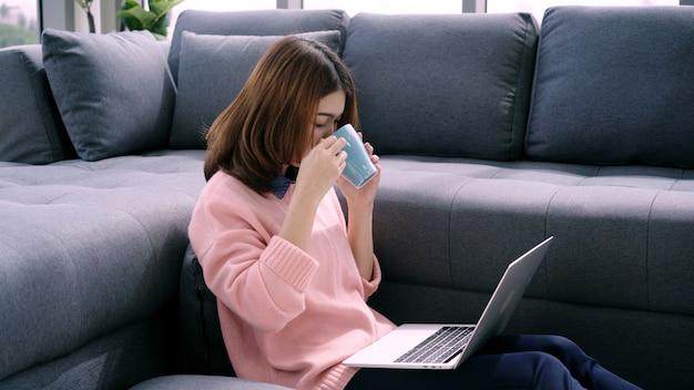 Porträt der schönen attraktiven asiatin, die den computer oder laptop hält einen warmen tasse kaffee oder einen tee verwendet
