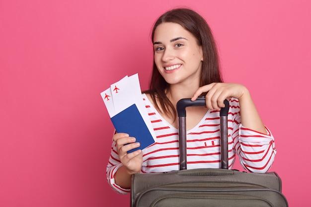 Porträt der schönen attraktiven eleganten weiblichen fröhlichen dame boarding, pass und ticket halten,