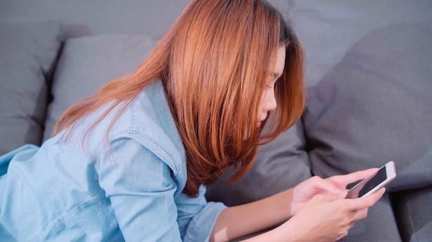 Porträt der schönen attraktiven jungen lächelnden asiatin, die smartphone beim lügen auf dem sofa verwendet
