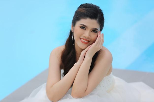 Porträt der schönen attraktiven lächelnden braut mit schönem langem hochzeitskleid gegen blauen farbhintergrund.