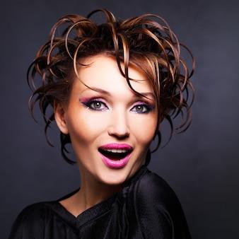 Porträt der schönen ausdrucksstarken frau mit modefrisur posiert.