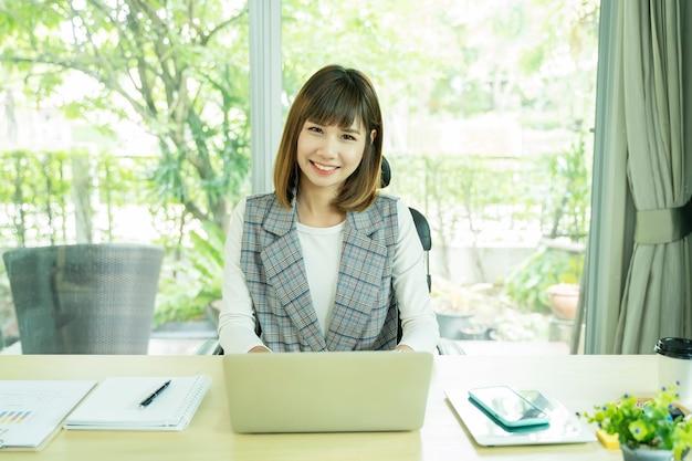 Porträt der schönen berufstätigen frau, die laptop mit zubehör auf schreibtisch verwendet