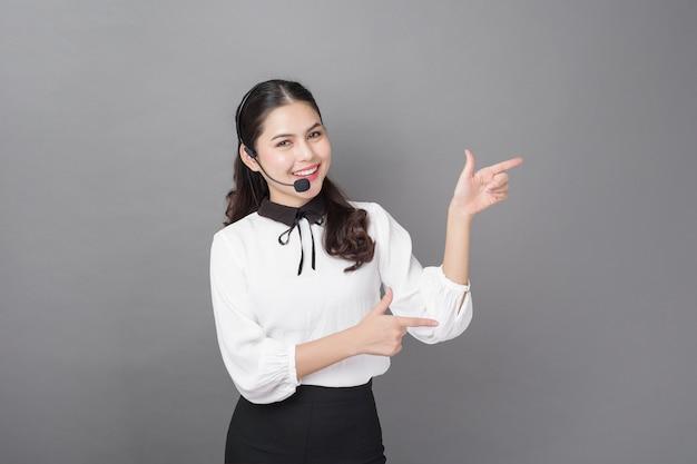 Porträt der schönen betreiberfrau auf grauer wand