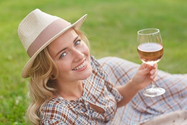 Porträt der schönen blonden frau, die lächelt und auf grünem gras liegt, während picknick im freien genießt