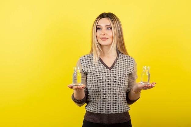 Porträt der schönen blonden frau, die zwei gläser stilles wasser hält.