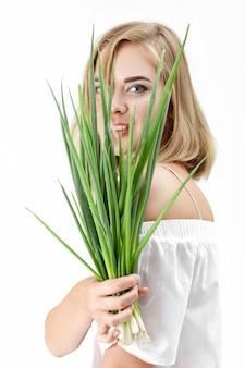 Porträt der schönen blonden frau in einer weißen bluse, die eine grüne zwiebel auf einem weißen hintergrund hält. gesundheit und vitamine