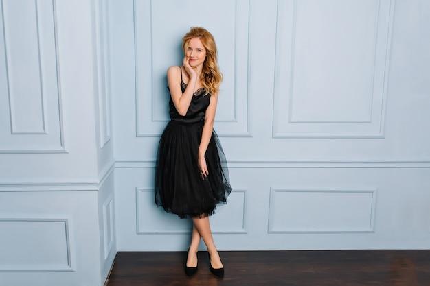 Porträt der schönen blonden frau in voller länge, die stilvolles schwarzes spitzenkleid und schuhe trägt, die im raum mit blauer wand aufwerfen. sie hat langes goldenes welliges haar.