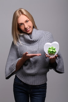 Porträt der schönen blonden frau mit herzförmiger geschenkbox