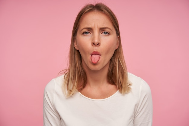 Porträt der schönen blonden frau mit lässiger frisur, die augenbrauen runzelt und ihre zunge zeigt, während sie über rosa hintergrund aufwirft, weiße bluse tragend