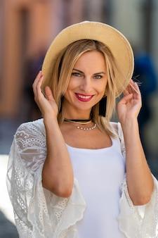 Porträt der schönen blonden frau mit sonnenhut kleidete in der hellen kleidung an. modisches mädchen, das im straßenhintergrund aufwirft