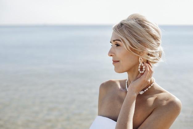 Porträt der schönen blonden kaukasischen frau am sonnigen tag nahe dem meer