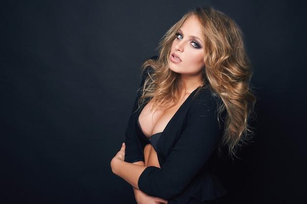Porträt der schönen blonden sexy frau auf schwarzem hintergrund