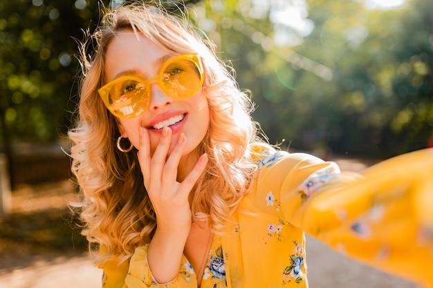 Porträt der schönen blonden stilvollen lächelnden frau in der gelben bluse, die sonnenbrille trägt, die selfie foto macht