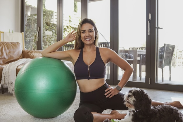 Porträt der schönen brasilianischen frau in sportbekleidung mit fitnessball und ihrem haustierhund, heimtraining, online-fitnessklassenkonzept