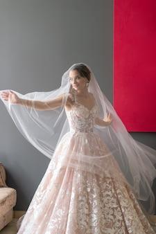 Porträt der schönen braut im weißen weinlesekleid, das unter schleier im studio aufwirft