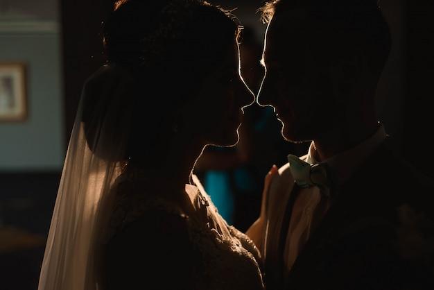 Porträt der schönen braut und des bräutigams gegen einen lichtstrahl.
