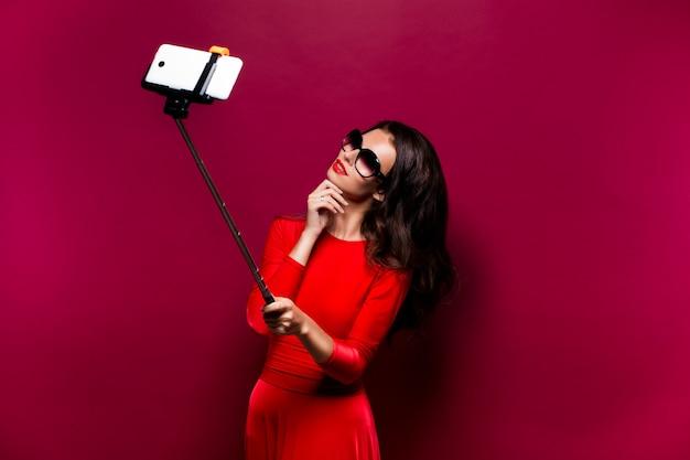 Porträt der schönen brünette im roten kleid und in den roten lippen, die sonnenbrille tragen, während selfie mit stock machen