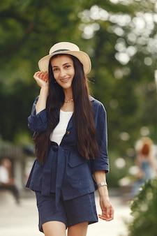 Porträt der schönen brünette. modell in der sommerstadt. frau in einem strohhut.