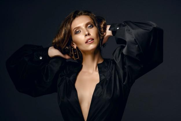 Porträt der schönen brünetten frau im schwarzen kleid