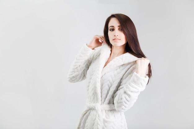 Porträt der schönen brunettefrau auf tragendem weißem bademantel des weißen hintergrundes