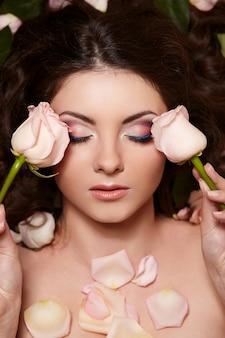 Porträt der schönen brunettefrau mit dem langen gelockten haar und den blumen