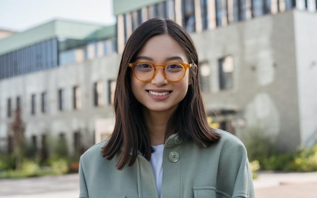 Porträt der schönen chinesischen frau, die stilvolle brillen trägt