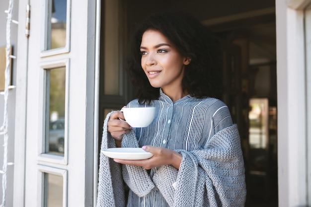 Porträt der schönen dame in plaid mit tasse kaffee in den händen gewickelt. nettes afroamerikanisches mädchen, das kaffee im restaurant trinkt