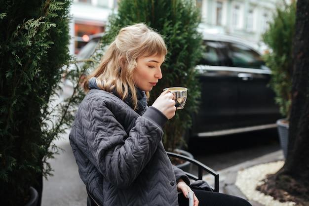 Porträt der schönen dame mit dem blonden haar, das kaffee auf stadtstraße sitzt und trinkt