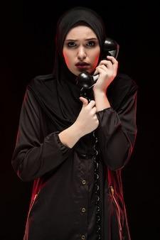 Porträt der schönen ernsten erschrockenen erschrockenen jungen moslemischen frau, die schwarzes hijab ruft um hilfe auf schwarzem trägt
