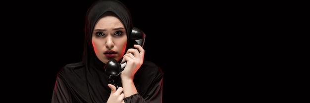 Porträt der schönen ernsten erschrockenen erschrockenen jungen moslemischen frau, die schwarzes hijab ruft um hilfe trägt