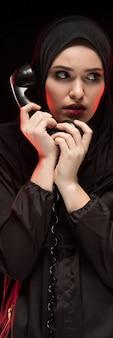 Porträt der schönen ernsten erschrockenen jungen moslemischen frau, die das schwarze hijab flüstert um hilfe auf schwarzem rufend trägt