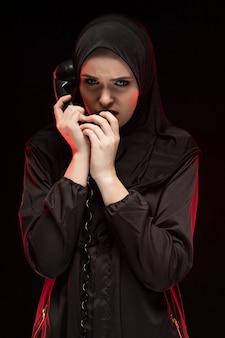 Porträt der schönen ernsten erschrockenen jungen moslemischen frau, die das schwarze hijab flüstert um hilfe auf schwarzem t-shirt rufend trägt