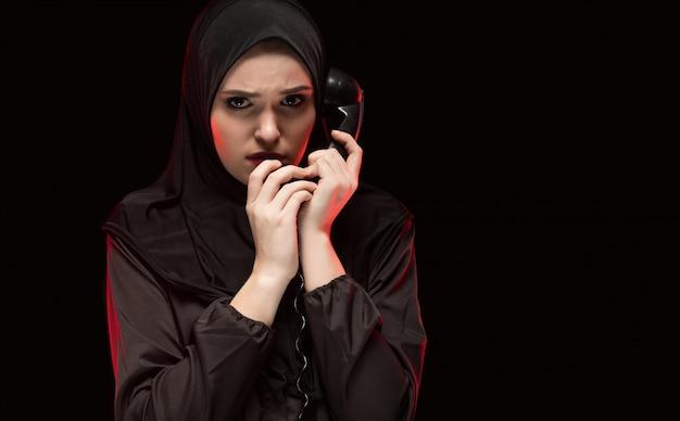 Porträt der schönen ernsten erschrockenen jungen moslemischen frau, die das schwarze hijab flüstert, um hilfe rufend trägt
