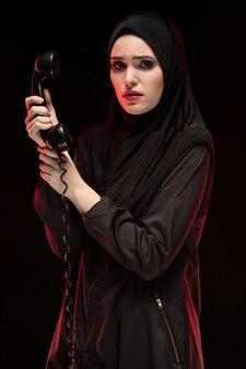 Porträt der schönen ernsten erschrockenen jungen moslemischen frau, die schwarzes hijab ruft um hilfe auf schwarzem trägt