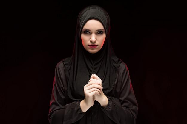 Porträt der schönen ernsten jungen moslemischen frau, die an hand schwarzes hijab mit als betendes konzept auf schwarzem hintergrund trägt