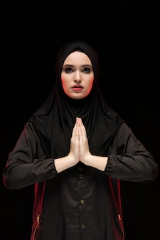 Porträt der schönen ernsten jungen moslemischen frau, die schwarzes hijab mit den händen nahe ihrem gesicht als beten trägt