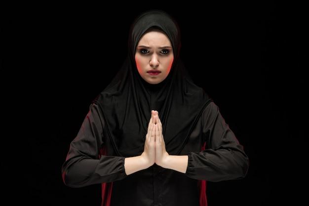 Porträt der schönen ernsten jungen moslemischen frau, die schwarzes hijab mit den händen nahe ihrem gesicht als betendem konzept auf schwarzem hintergrund trägt