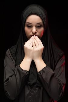Porträt der schönen ernsten jungen moslemischen frau, die schwarzes hijab mit den händen nahe ihrem gesicht als betendem konzept auf schwarzem trägt
