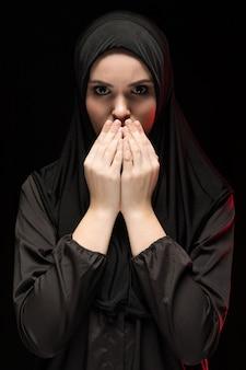 Porträt der schönen ernsten jungen moslemischen frau, die schwarzes hijab mit den händen nahe ihrem gesicht als betendem konzept trägt