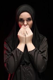 Porträt der schönen ernsten jungen moslemischen frau, die schwarzes hijab mit den händen nahe ihrem gesicht als betendem konzeptschwarzem trägt