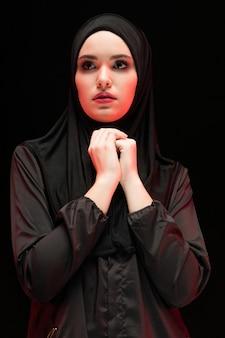Porträt der schönen ernsten jungen moslemischen frau, die schwarzes hijab mit den händen nahe ihrem gesicht trägt, wie konzept beten
