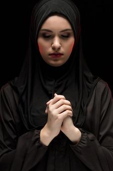 Porträt der schönen ernsten jungen moslemischen frau, die schwarzes hijab mit geschlossenen augen als betendem konzept auf schwarzem hintergrund trägt