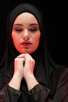 Porträt der schönen ernsten jungen moslemischen frau, die schwarzes hijab mit geschlossenen augen als betendem konzept auf schwarzem trägt