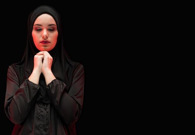 Porträt der schönen ernsten jungen moslemischen frau, die schwarzes hijab mit geschlossenen augen als betendem konzept mit copyspace trägt