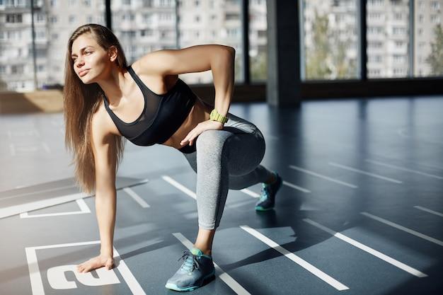 Porträt der schönen erwachsenen fitness-trainerin, die sich am morgen im fitnessstudio ausdehnt und den sonnenaufgang betrachtet, motiviert, einen perfekten körper für ihre kunden zu erhalten.