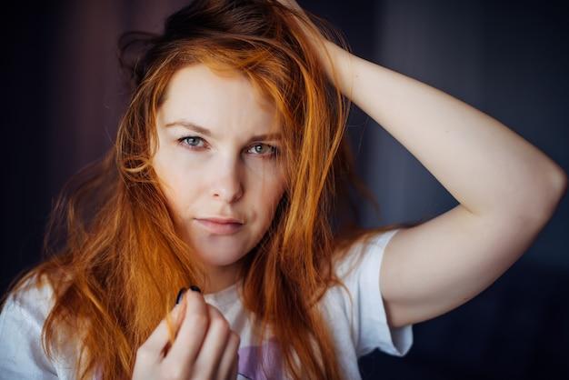 Porträt der schönen erwachsenen jungen frau mit dem roten zerzausten haar, nahaufnahme, unscharfer hintergrund. sexy brünette berührt ihr langes haar und schaut in die kamera. Premium Fotos
