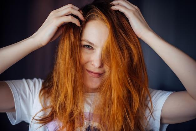 Porträt der schönen erwachsenen jungen frau mit dem roten zerzausten haar, nahaufnahme, unscharfer hintergrund. sexy brünette berührt ihr langes haar und schaut in die kamera.