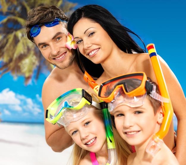 Porträt der schönen familie des glücklichen spaßes mit zwei kindern am tropischen strand mit schützender schwimmmaske